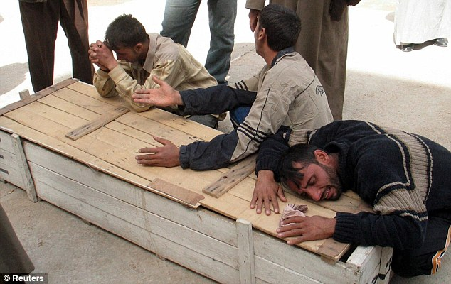 men mourn over the coffin of a victim of Sad'r city's bombings in the holy city of Najaf