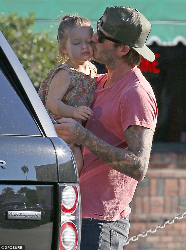 Doting: David Beckham was seen kissing daughter Harper during a shopping trip in Los Angeles