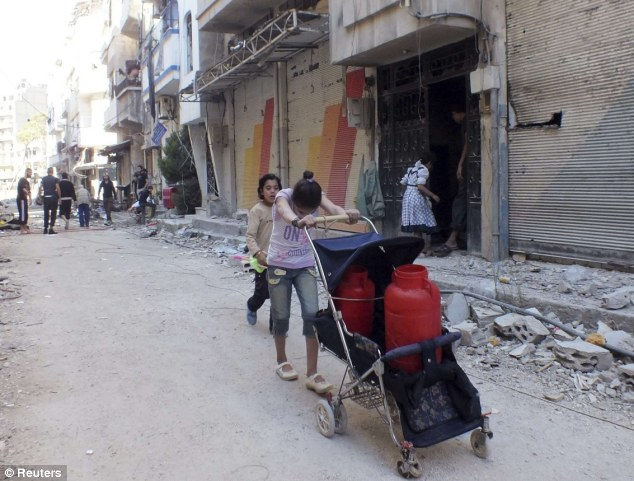 Chilling game: A British surgeon has revealed that snipers are targeting women and children as they fetch food and supplies. such as here in Homs where a girl is seen collecting water