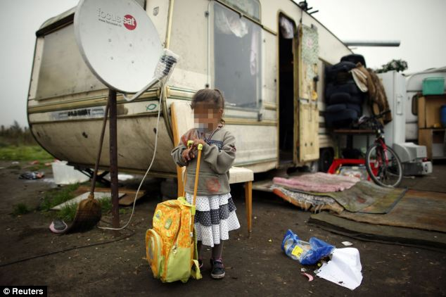 Una chica se apoya en una escuela mochila fuera de una caravana en un campamento de las familias gitanas en Triel-sur-Seine, cerca de París