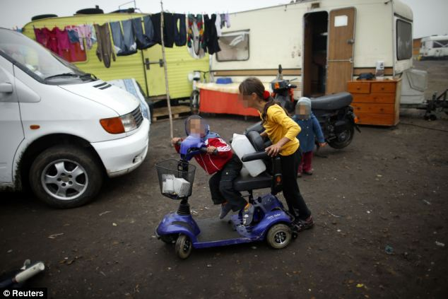 """""""Vinimos aquí para alimentar a los niños: Tres niños juegan delante de sus caravanas en un campamento de las familias gitanas en Triel-sur-Seine, cerca de París"""