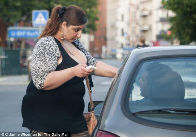 Otra prostituta Roma habla a un hombre a través de la ventana de su coche en Berlin