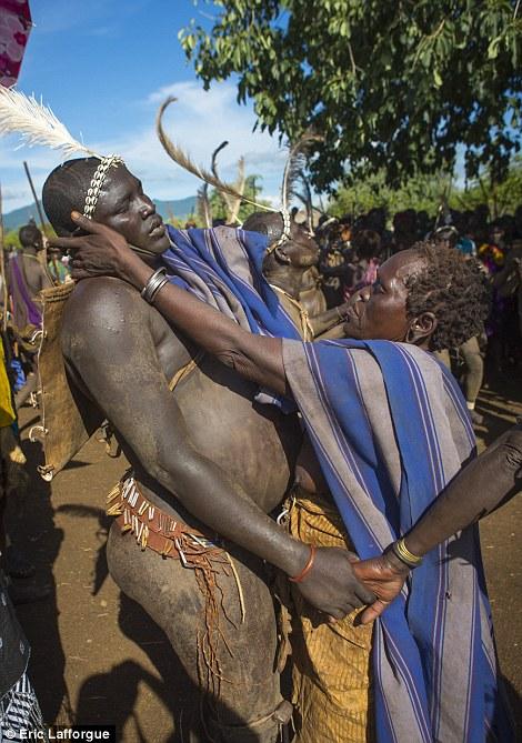 Uma mulher Bodi enxuga o suor de um dos homens gordos