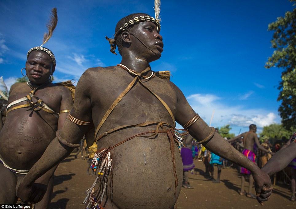 Sacred: Os homens gordos correr ou caminhar em torno da árvore especial da aldeia, visto por anciãos da tribo e outros homens, e ajudou pelas mulheres