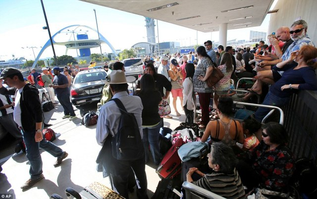 Passengers wait for Los Angeles International Airport to reopen at Terminal 1 on Friday following a gunman going on a shooting spree at terminal 3