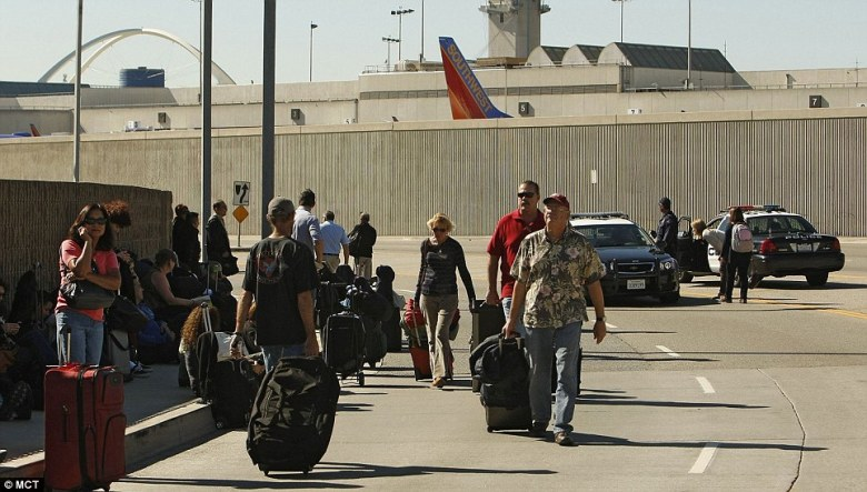Passengers with their luggage leave LAX after a suspect believed to be armed with an assault rifle opened fire inside Terminal 3 at Los Angeles International