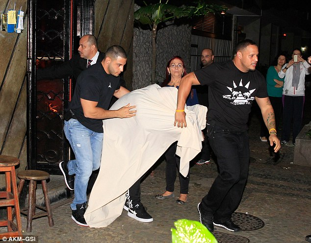 Now you see him: Justin Bieber exits a Brazilian brothel where fans had already gathered to catch a glimpse of the star