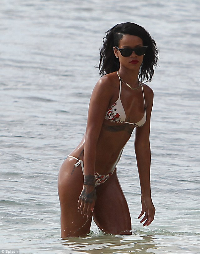 Sleek: The singer wore a white and floral print bikini with RayBan Wayfarers