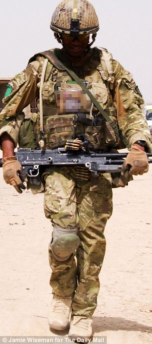 Constant danger: A British soldier on patrol in the village of Chah e-Anjir in Helmand. Many soldiers serving there in 2011 were deeply affected