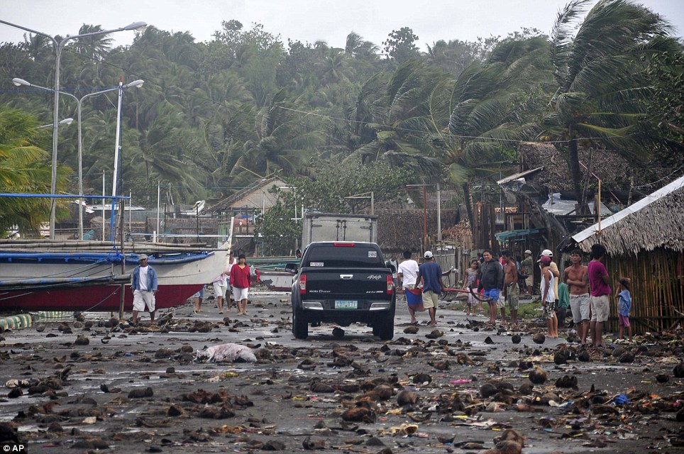 Devastation: Debris which was washed in by the storm litters the road by the coastal village in Legazpi city. Residents now face a long clean up operation to repair the damage to their homes