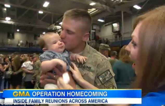 Meeting daddy: Captain William Lotts kisses his three-month-old daughter Finley after meeting her for the first time, as his wife Brittany looks on. He returned from a 9-month deployment to Afghanistan