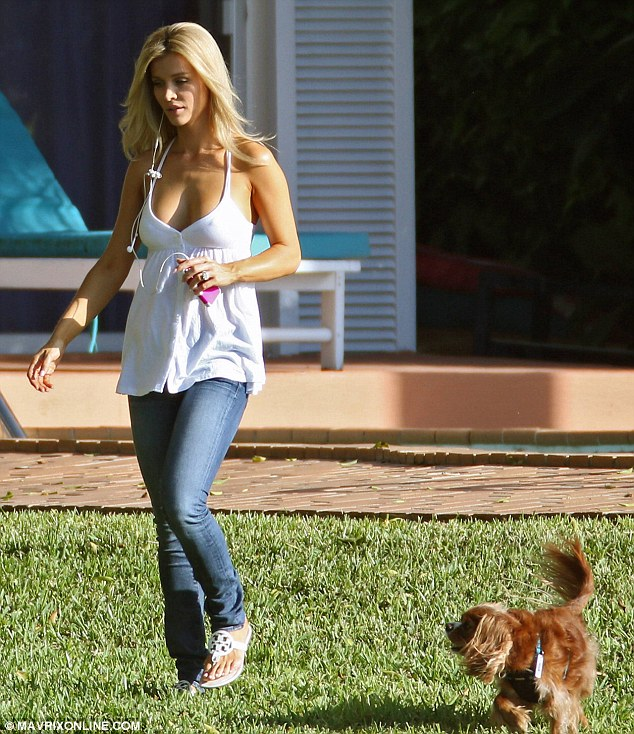 Multitasking: The 34-year-old was plugged into her iPod while strolling across the lawn with Darla