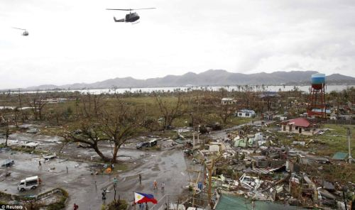 Debris: Helicopters hover over the damaged area of Tacloban city, which was battered with strong winds yesterday