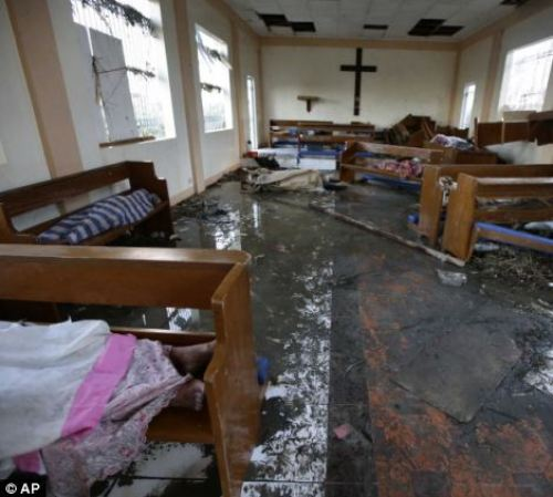Bodies wrapped in blankets are placed inside a damaged chapel