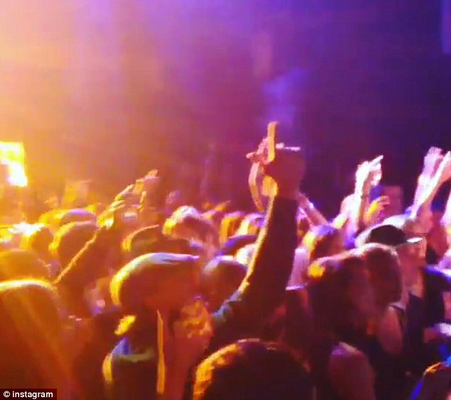 Rocking out: Leo is seen making 'gun fingers' as dances in a crowd of people at the club in New York