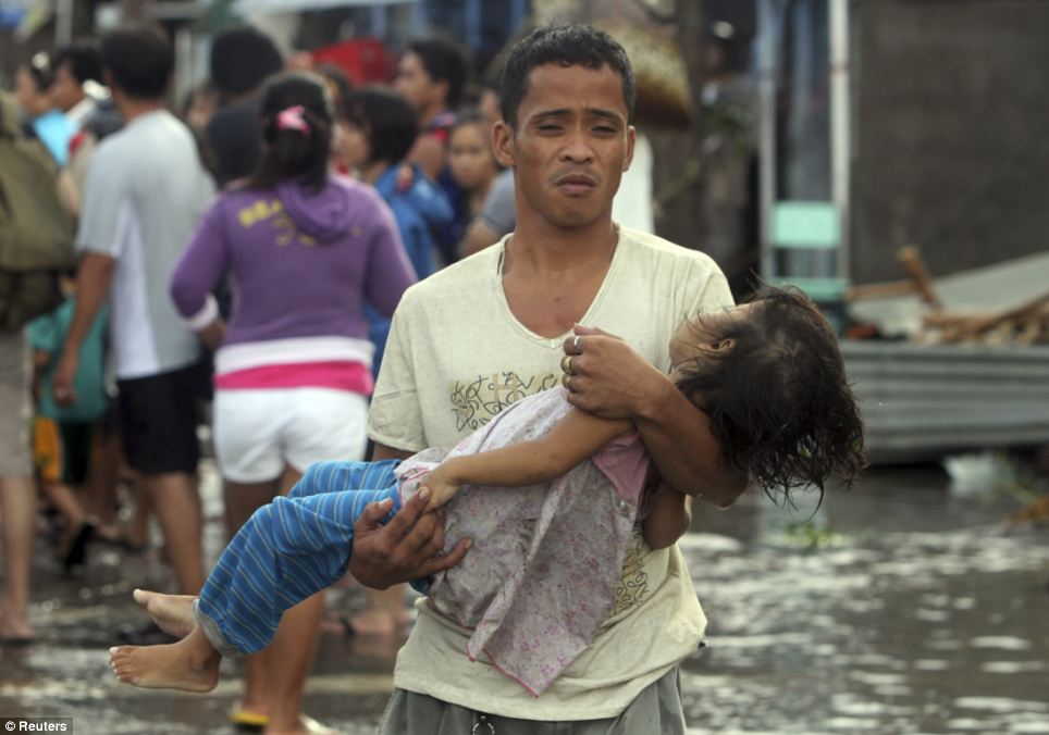 A father carries the lifeless body of his daughter on the way to the morgue after super typhoon Haiyan hit Tacloban City in Leyte province