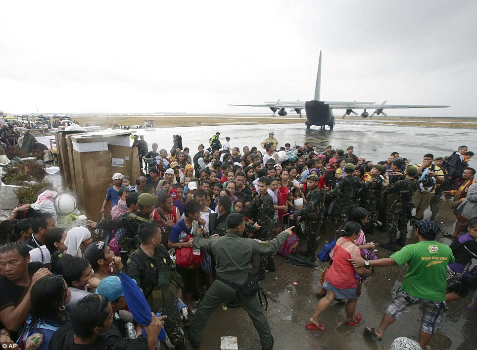 Everybody rushes to get a chance to board a C-130 military transport plane in Tacloban city
