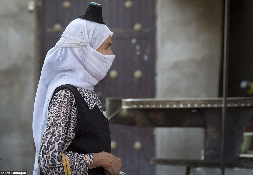Defiance: This elderly woman, photographed in the city of Kyria, is wearing a banned Taipak - the world's smallest hat - on top of her equally illegal veil