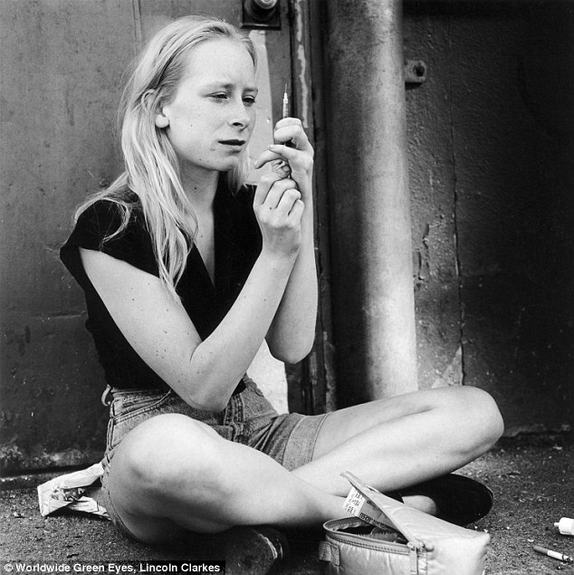 Addiction: A young woman prepares to inject heroin as she sits cross-legged on the sidewalk