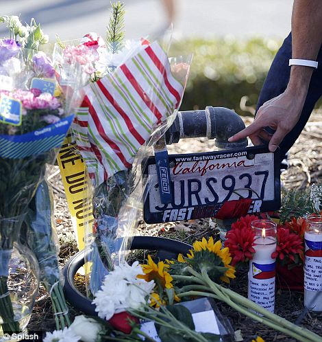 People lay flowers at the spot where actor Paul Walker died in a car accident in Santa Clarita, CA.