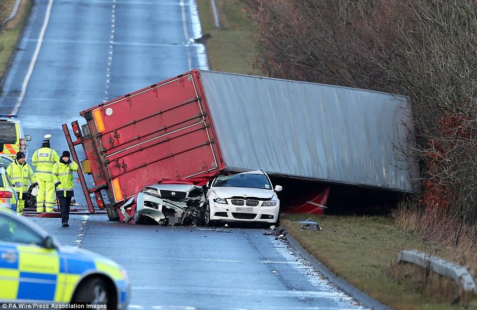 Aplastado: La policía en la escena en la que un camionero murió después de que su HGV derrocó a un número de coches en la A801 en West Lothian como vientos trajeron interrupción