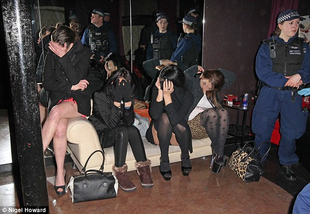 Crime hotspot: Women, believed to be sex workers, cover their faces as they wait to be questioned by police during a major crackdown on drugs, prostitution and human trafficking in Soho, London