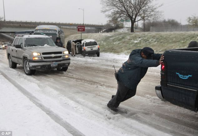 Trouble: Vehicles are pushed up a slick hill in Fort Worth, Texas. The ice has already claimed one life on the roads