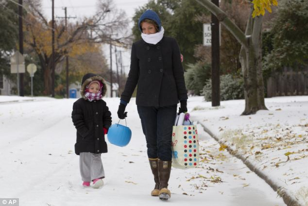Bundled up: Ashley Leonard and her daughter Veda, 4, walk to a neighbor's house for pancakes along an icy street in Fort Worth, Texas on Friday as they wrapped up against 'Ice Friday'