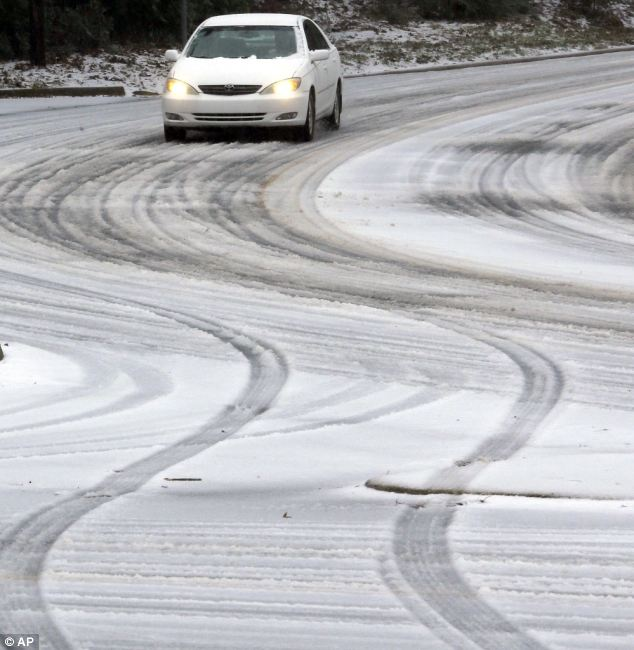 Daunting: A car makes its way down a sleet-coverd hill in Little Rock, Arkansas on Friday morning