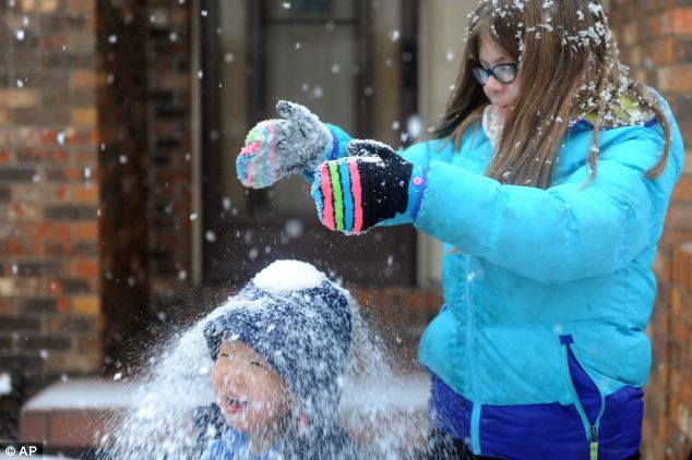 That's just cold: Olivia Aurs, 9, dumps a handful of snow on her three year-old brother, Alex Aurs' head as they play in the snow in the Lakeside Terrace subdivision in Evansville, Indiana