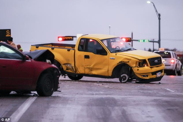 Smash: Police and tow trucks remove wrecked vehicles off the road Friday morning in Austin, Texas