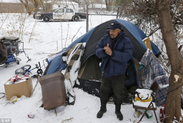 Waiting it out: Jack Fontenot rubs his hands to warm them after coming out of a tent at a homeless encampment in Oklahoma City. Some of the people who live here refuse to leave their tents for a shelter