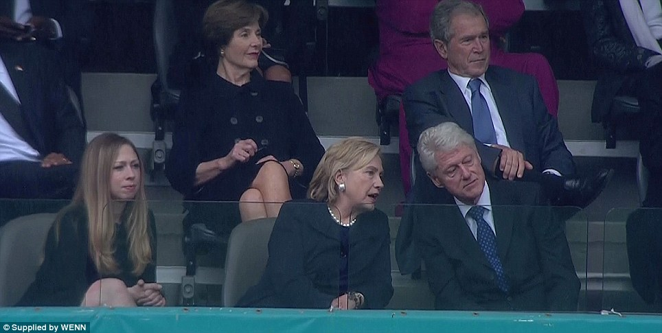 Front-row seats: Chelsea Clinton sits with her parents former president Bill and Hillary Clinton at the memorial service in Johannesburg as George W and Laura Bush look on