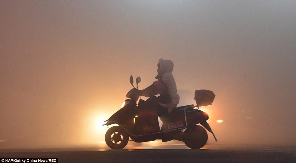 Danger: Un motard tente de vaquer à leurs affaires comme d'habitude à Fuyang, province de l'Anhui, où le niveau de pollution IQA est actuellement de 245 ou «très mauvaise».  En dessous de 50 est sans danger
