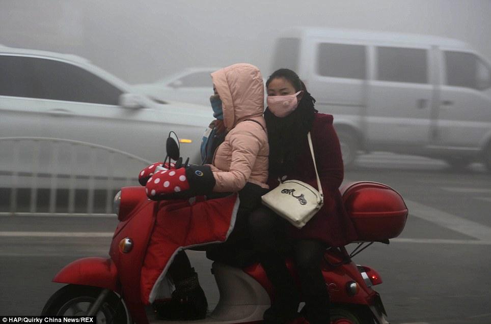 Recouverts: Les femmes portent des masques en tissu de fortune pour se protéger contre la bande de smog dans Xuchang, province du Henan, où la pollution a également atteint des niveaux nocifs