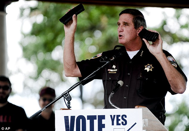 Not enforcing: Weld County Sheriff John Cooke holds up two identical rifle magazines, one obtained legally and one obtained illegally, while making a speech to supporters of the recall election to oust Senate President John Morse in Denver