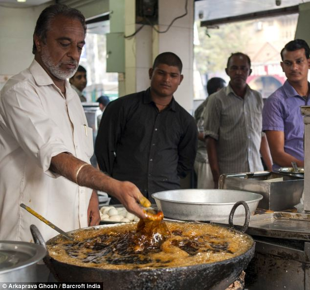 Hot act: Prem Singh sinks his fingers into the scorching oil while cooking at a restaurant in New Delhi, India, as amazed customers look on