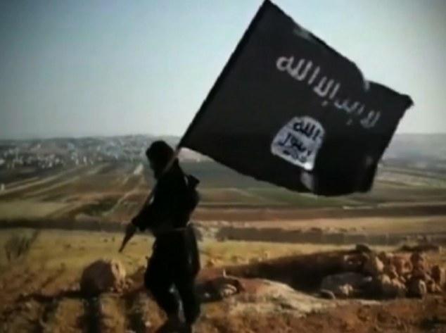 Groupe Al-Qaïda: Un homme tenant le drapeau de l'Etat islamique en Irak et al-Sham (ISIS) marche à travers une colline dans une vidéo de propagande pour l'organisation