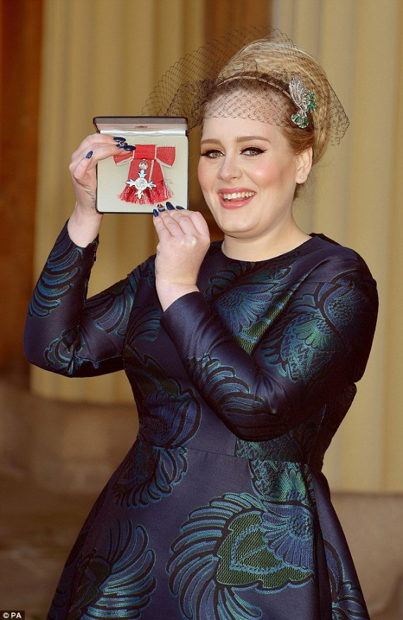 Best of British: Miss Adele Adkins MBE holds her honour aloft at Buckingham Palace on Thursday