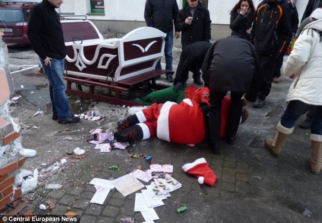 Smashed: The Santa is helped from the wreckage of his sleigh after his wild ride through Ustrzykach Dolnych