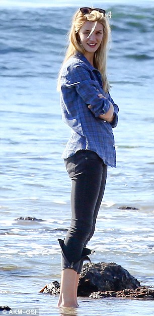 Effortlessly chic: Rosie wore a checked shirt with black skinny jeans as she dipped her feet in the ocean