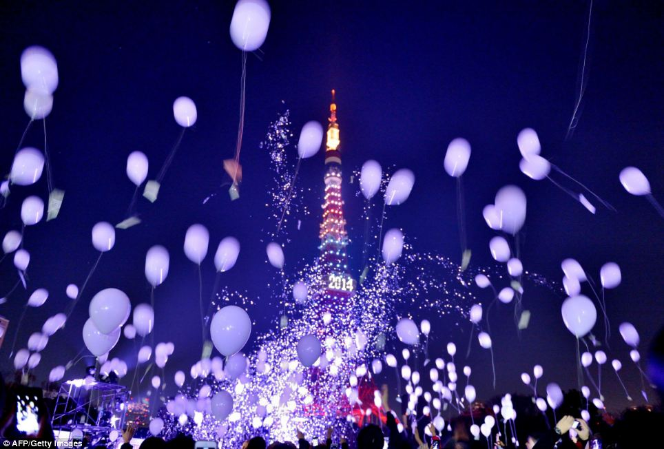 Thousands release balloons into the sky as the Tokyo is illuminated during the countdown to midnight in Japan's capital