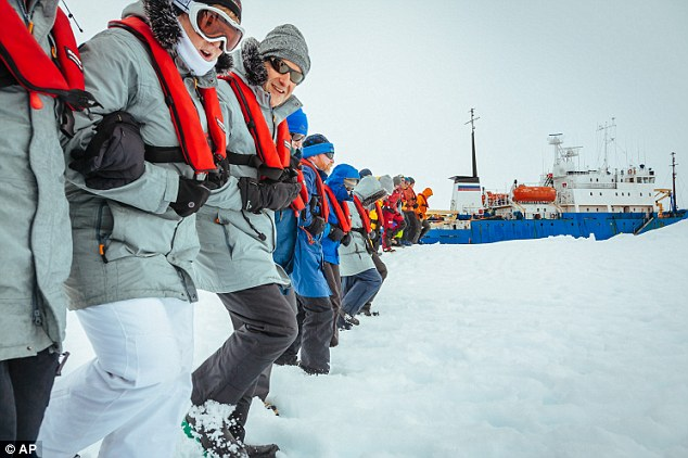 Stuck: Passengers from the Russian ship MV Akademik Shokalskiy link arms and stamp out a helicopter landing site on the ice near the trapped ship 1,500 nautical miles south of Hobart, Australia