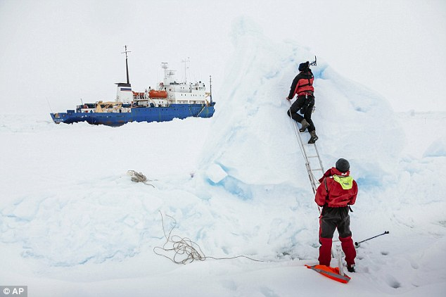 Trapped for more than a week: Ben Maddison and Ben Fisk from MV Akademik Shokalskiy work to place a wind indicator atop an ice feature near the trapped ship