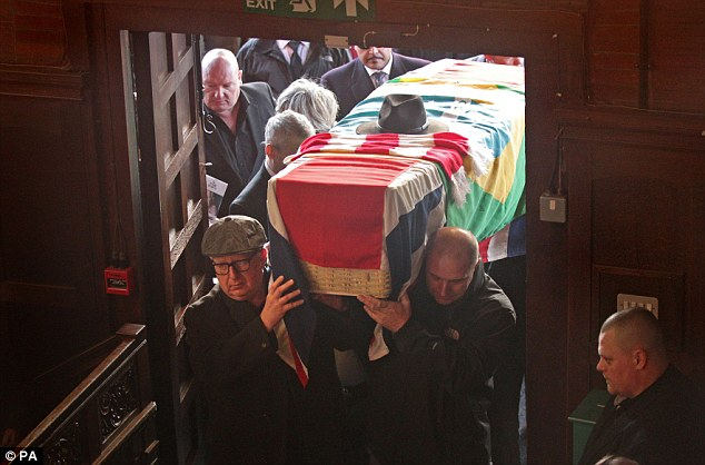 The Great Train Robber's coffin, draped with a Union Flag, a Brazilian flag and a scarf of his beloved Arsenal football team is carried into Golders Green Crematorium