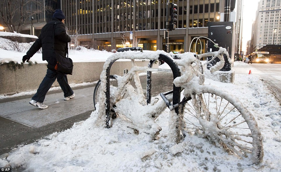 A man walks past a snow encrusted bicycle with wind chills nearing minus 30F on Tuesday, in downtown Chicago