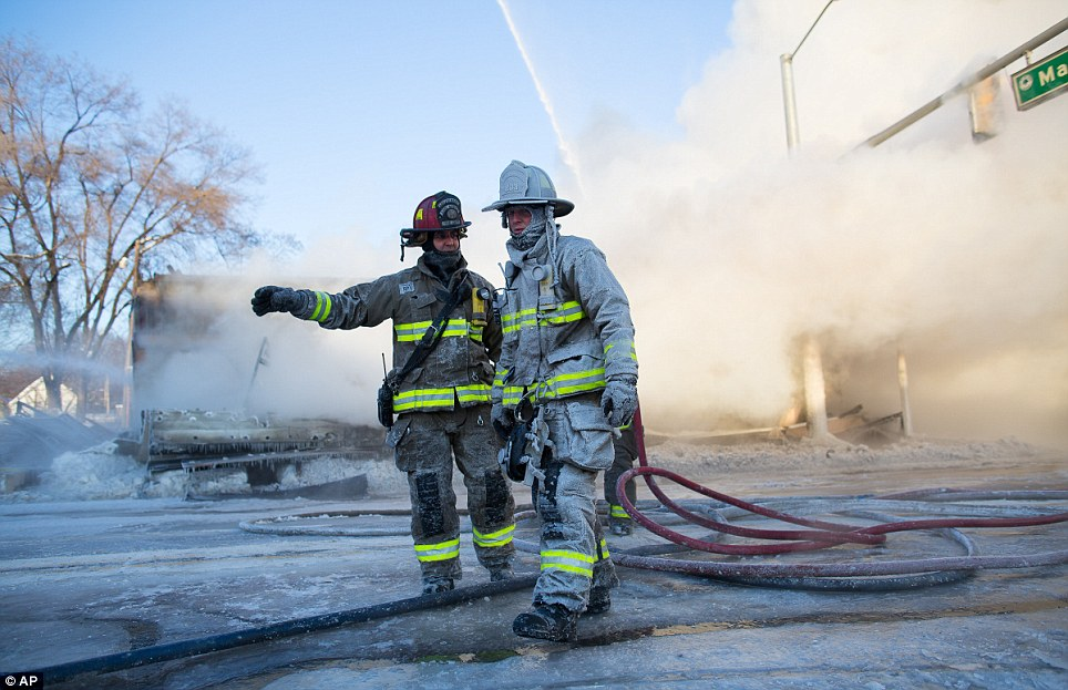 Ann Arbor firefighters covered in ice work to put out a fire that engulfed Happy's Pizza in Michigan on Tuesday