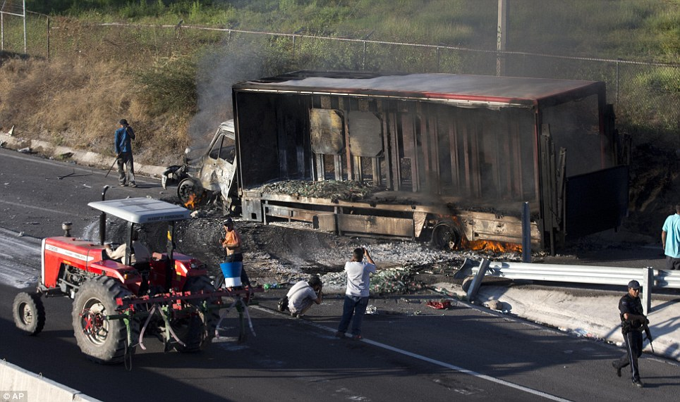 Torched: A vehicle burns at an entrance to Paracuaro, Mexico, on Thursday as part of a protest by residents at the arrival of vigilantes