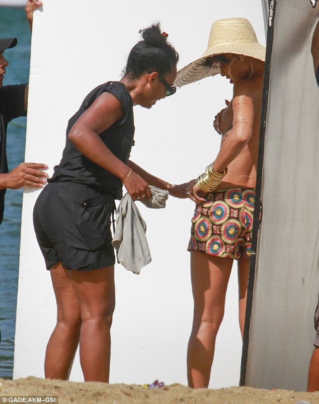 Getting the look right: Despite the small amount of clothing, a large team was on hand to ensure Rihanna looked her best