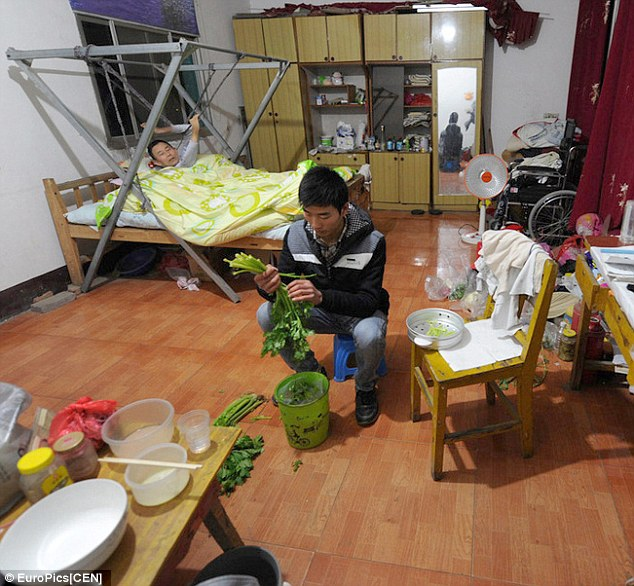 Chinese student Guo Shijun (right) prepares a meal for his father in his dorm while his father (left), who is paralysed from the waist down, rests in the specially installed bed